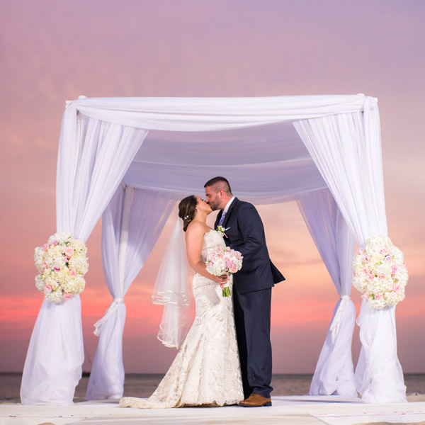 ceremony arch with bride and groom at sunset